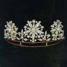 An earlier belle epoque tiara, circa Designed as a series of three diamond flower heads, with five main petals and five lesser petals, surrounded by a ring of circular diamonds; with fleur de lys spacers. Royal Crowns, Royal Tiaras, Tiaras And Crowns, Diamond Tiara, Rose Cut Diamond, Diamond Flower, Royal Jewelry, Fine Jewelry, Antique Jewelry