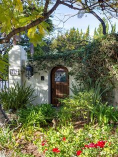 Charming stucco wall with arched door to patio in 1927 Spanish Colonial Revival home. 2012 Pasadena Showcase property.