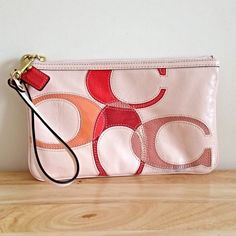 Authentic Coach Wristlet Authentic COACH medium size signature wristlet. Pale pink coloring with warm coloring along the logo. Has red leather Coach key chain.  Zipper closure. Very slight scuff mark on back. Coach Bags Clutches & Wristlets