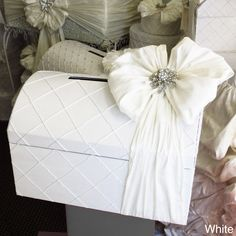 This fabulous hand assembled envelope box in the shape of a treasure chest comes in either ivory or white. It includes a bow with a crystal brooch that holds the chest shut and a convenient slit in the lid allows people to put envelopes inside.