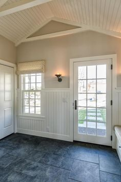 HGTV features this cottage-style mudroom with pitched white ceilings, beadboard wainscoting, a windowed door and gray slate floors.