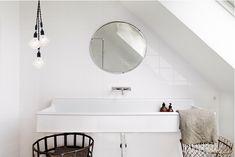 white tile, round mirror, trough sink, edison bulbs