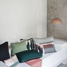 Une suspension style scandinave très sobre au dessus d'une banquette avec des coussins colorés, Ferm Living
