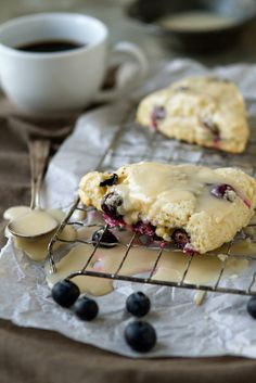 Blue Berry Lemon Scone 1/3 cup sugar  zest of two medium lemons  2 cups all-purpose flour  1 teaspoon baking powder  1/4 teaspoon baking soda  1/2 teaspoon salt  8 tablespoons unsalted butter, frozen  1/2 cup sour cream  1 large egg  1 cup fresh/frozen blueberries  For the Glaze  3 tablespoons unsalted butter; melted  1 cup confectioners' sugar; sifted  1/2 teaspoon pure vanilla extract  2 tablespoons freshly squeezed lemon juice