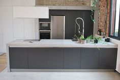 concrete worktop/ island. Like the texture from the bricks. Grey is a bit dark