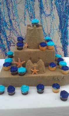 Mermaid Party- sand castle cupcake stand  Cardboard, plastic castle pieces, spray adhesive and sand  Ribbon seaweed- two spools of ribbon curled