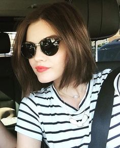 Lucy Hale raspberrily smiling in black horn-rimmed shades, brown lob, B&W striped tee