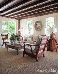 Designer Shawn Henderson updated the living room of this 1830s colonial farmhouse in Hillsdale, New York, by painting the wood walls white but leaving the ceiling beams dark. Then he filled the space with furniture picked up at yard sales and antique stores. - HouseBeautiful.com