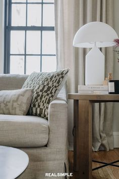 30 Easy and Chic Living Room Decorating Ideas for Any Sized Space | A neutral living room gets a bit of contrast from black window frames. The designers at J.Miller Interiors are masters at making clean lines and tone-on-tone texture feel relaxing and calming, yet still fresh. #realsimple #livingroomdecor #livingroomideas #details #homedecorinspo
