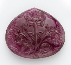 Stunning Large Carved Rubellite Tourmaline  Brazil   It has become very difficult to find rubellites with strong color in such a large size. Hand-carved in India, decorated to the front with a carving of three lotus flowers and to the reverse with a stylized single lotus blossom, the quality of the tourmaline used in this rich deep purplish pink tourmaline is exceptional.  Weighing approximately 220.5 carats, height 4.3cm