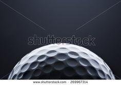 Stylish golf ball isolated on empty dark blue background, close up shot with…
