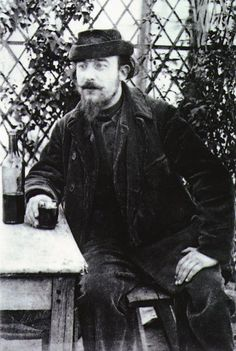 Erik Satie (composer)at a table in the park of the Moulin de la Galette. Photograph by Santiago Rusiñol, 1892.