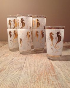 These Hazel Atlas nautical mid century high ball glasses have shiny gold seahorses on a white frosted background