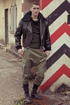 Ce look d'inspiration militaire a beaucoup de caractère. Le pantalon kaki est particulièrement intéressant : c'est un mélange entre un saroual et un cargo. S'arrêtant à la moitié du mollet, il vient se casser sur une paire de rangers traditionnelles à double boucle. Quant au perfecto, c'est lui qui vient apporter du corps à la tenue. On apprécie particulièrement son col rabattu en laine tricotée. #modehomme #menswear #perfecto #cargo #saroual