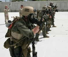 Marines practice marksmanship with their while wearing gas masks