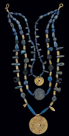 A WESTERN ASIATIC LAPIS LAZULI AND GOLD BEAD NECKLACE   CIRCA LATE 3RD-2ND MILLENNIUM B.C.   Composed of biconical, spherical, disk-shaped, crescent-shaped and pendant lapis lazuli beads, interspersed with ribbed sheet gold cylindrical and pendant beads, strung in three strands, two centered by sheet gold disk pendants, circa 1000 B.C., each with the star of Astarte, one centered by a large lentoid lapis lazuli bead; with a modern hook-and-loop closure  18 in. (45.7 cm.) long