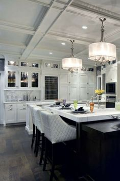 Contemporary luxury kitchen with white stools, marble island counter, white coffered ceiling and more.