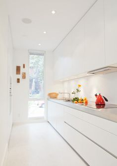 The galley kitchen, in classic white, is the one splurge within the interior: it was custom made by Bulthaup from their B1 series. A narrow window, with a frosted bottom panel, balances views and privacy.