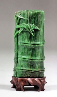 A Chinese spinach green jade bamboo pattern spill vase, with vivid striations, 4.375ins (112mm) high, and wood stand