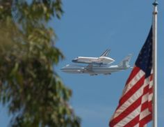 Space Shuttle Endeavor flying over Grand Park in Los Angeles, CA on its final journey today (9/21/2012).  Nicely framed photo with American Flag in the foreground.  #nasa #spottheshuttle #endeavor