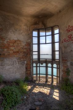 The abandoned tower window inside the hospital on the deserted island of Poveglia, a stone's throw from Venice, Italy.