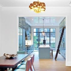 A pendant fixture by C. Jeré hovers above the dining area in this renovated West Village townhouse by Mark Zeff. Calacatta gold marble tops the kitchen cabinets, a welcome material contrast to the iron-framed windows where sunlight pours in. : Eric Laignel. #architecture #interiors #design #interiordesign #westvillage #townhouse #nyc... - Interior Design Ideas, Interior Decor and Designs, Home Design Inspiration, Room Design Ideas, Interior Decorating, Furniture And Accessories