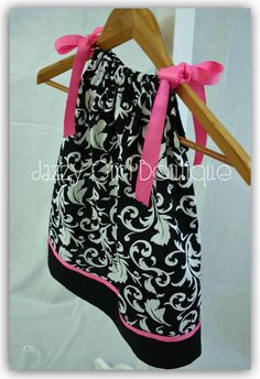 Girls pillowcase dress made from a black & white scroll fabric with a solid black border. I have added a bright pink around the bottom and as the ribbon ties for that pop of color. These dresses are so versatile! Loosen the ribbons as your child grows so she can wear it for several years. Once it...