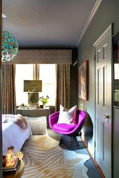 Purple chair in corner of bedroom with modern light fixture, cowhide rug, and retro curtains