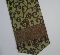 Elegant designer table runner in a green and brown abstract floral fabric with a slight crinkle is enhanced with a chenille animal print inset and further highlighted with decorative trims. The back lining is of a coordinating fabric. Size: 74 in x 17 in