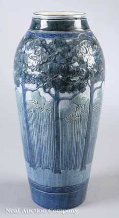 An Important Newcomb College Art Pottery High Glaze Vase , 1908, decorated by Leona Nicholson with a landscape of tall pine trees, blue and blue-green underglaze, base marked with Newcomb cipher, decorators mark, reg. no. CO-31, and W for white clay body, retains partial original paper label which is obscuring the potters mark, height 12 3/4 in
