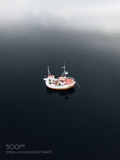 Fishermens boat in the middle of the deep fjords water by Lyes