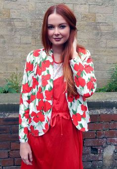 This gorgeous vintage jacket looks great dressed up with a cocktail dress or dressed down with jeans. Collared edge to edge style in a rich blend non stretch cotton. White with beautiful bold red and green print. A stunning statement vintage piece.