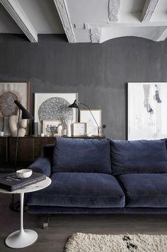 dark navy velvet sofa against a dark grey wall with white art