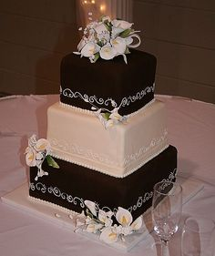 Square Wedding Cake with gumpaste calla lillies - This is a square wedding cake covered in ivory and chocolate fondant with scroll work and gumpaste flowers. TFL!