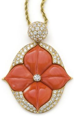 A coral and diamond necklace by Mauboussin. Designed as a stylised lotus flower, the carved coral petals set to the centre with a brilliant-cut diamond within a pavé-set diamond oval frame, suspended from a domed similarly set diamond surmount, to a twisted ropework chain, length 70 cm, pendant length 5.7 cm, signed 'Maubaussin, Paris'. Accompanied by a blue suede Mauboussin case. Via Phillips.