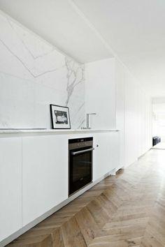 mur en marbre blanc, sol en parquet clair, meubles de cuisine encastrés, mur en marbre blanc