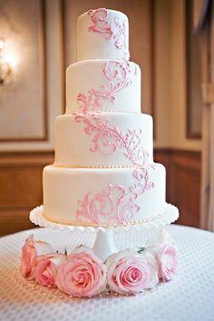 Torta de boda de fondo blanco con perlas y decoracion con patrones de color rosa.