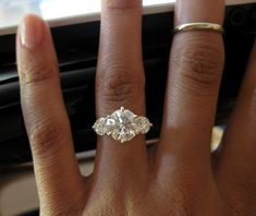 3 ct center stone with .5 ct on either side with channel diamond band with hearts in band.