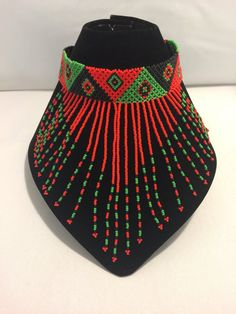 Beaded choker with a beaded ball and loop closure. Choker measures approximately 11.8 inches (15 inches including loop and beaded ball closure). Hand beaded by the young Zulu women from Durban, South Africa.  *While all efforts are made to show the jewelry as accurately as possible, dimensions and colors may vary slightly.