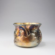 Louis C. Tiffany, New York. 'Lava' vase, 1908. H. 11.5 cm. Cased glass, almost black fusions, lava-like rough, textured appliquations, leaves and twigs, strong matt gold and mother of pearl lustre. Signed: L. C. Tiffany - Favrile 2571 C