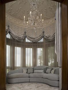 Opulence is easy to live with if you know how to use adornment without sacrificing comfort. This luxury master bedroom sitting area for Malinard Manor designed by Cravotta Studios Interior Design aims high with most of the ornamentation on the upper walls and ceiling and a cushy couch and plush rug grounding the look down below.