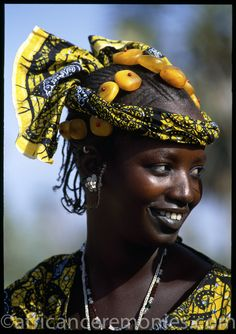 Africa | A young Fulani Woman has adorned herself with colorful cloth and amber jewellery to catch the eye of the herders returned from the long cattle drive.  Mali | ©Angela Fisher and Carol Beckwith (African Ceremonies)