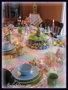 Easter bunny and eggs. Centerpiece: bunny figurine on pedestal plate, set inside an egg wreath.  Easter grass and plastic eggs surround bunny. Nice table setting.