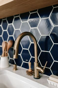 Navy blue hex tile with gold faucet