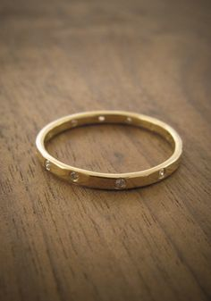 Simple gold hammered hand made band. bezel set stones around ring. stacking or engagement ring