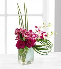 Cosmopolitan Bouquet-Fuchsia dendrobium orchids, purple alstroemeria and purple carnations showcase this cosmopolitan design. Equisetum and lily grass accent this graceful bouquet that's arranged in a contemporary glass vase. A truly elegant gift. Purple Carnations, Pink Orchids, Flower Arrangements Simple, Orchid Arrangements, Orchid Bouquet, Floral Bouquets, Flowers Today, Online Florist, Dendrobium Orchids