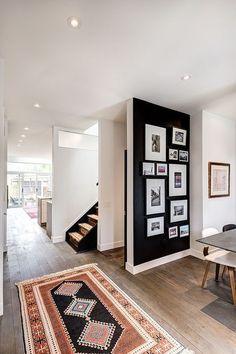 casa decorada com tapete étinico e parede preta com quadros do chão até o teto