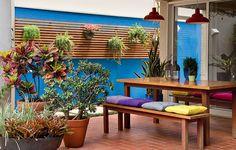 A parede azul foi um pedido da moradora à paisagista Susana Bandeira, da Maria Flor Paisagismo e deu um toque litorâneo ao espaço. Ali, convivem espécies variadas e, entre elas, um vaso de bálsamo (ao centro, próximo ao banco)