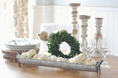 A simple white pumpkin centrepiece in a long galvanized metal trough with baby's breath and twinkle lights among a tables cape of wooden candlesticks, wood slices white dishes and a boxwood wreath, Galvanized Tray Centerpieces, White Pumpkin Centerpieces, Farmhouse Table Centerpieces, Lighted Centerpieces, Diy Farmhouse Table, Table Decorations, Galvanized Trough, Metal Trough, Galvanized Metal