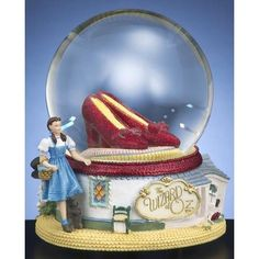 """*The most famous pair of shoes rotate around on this San Francisco Music Box Wizard of OZ Ruby Slippers Waterglobe. Features wind up 18-note movement.    Tune: """"Over The Rainbow"""""""